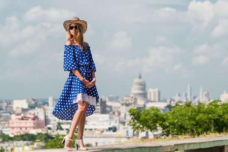 Young beautiful woman with blond hair, dressed in long blue dress and straw hat is standing on the curb on the background of the landscape of the city Havana at summer sunny day Stock Photo
