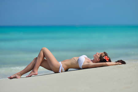 Beautiful pretty young girl with flower in her long brown hair and white swimsuit is lying on the beach. Chrystal azure water of caribbean sea at coastline at summer sunny day.