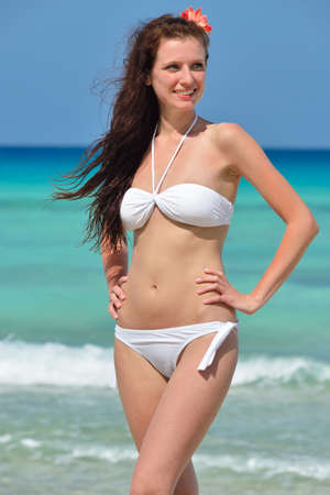 Beautiful handsome young girl with flower in her long brown hair and white swimsuit is standing on the beach, and watching aside. Chrystal azure water of caribbean sea at coastline at summer sunny day.