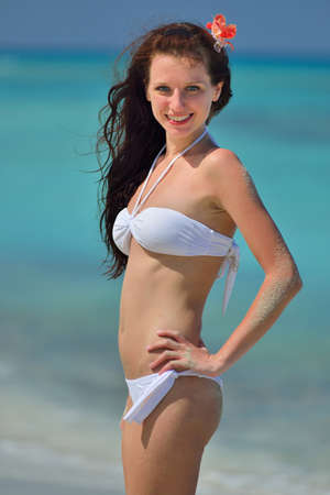 Beautiful pretty young girl with flower in her long brown hair and white swimsuit is standing on the beach. Chrystal azure water of caribbean sea at coastline at summer sunny day.