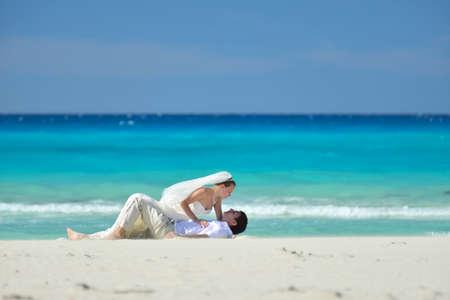 varadero: Wedding couple is lying on the sand of the coast of the caribbean sea Stock Photo