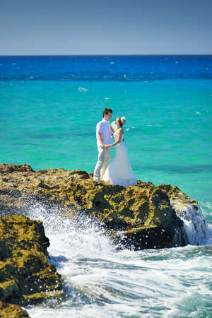 The couple is standing at the oceanfront. The waves are beating against the rocks.