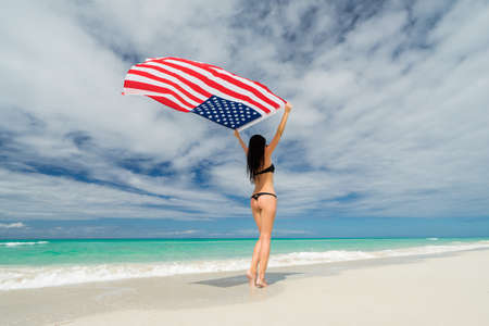 Beautiful young woman in black bikini swimsuit is standing a back on a beach on the background of azure sea and holding a flag of USA in her arms. Hot summer day at the caribbean coastline.