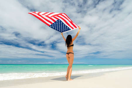 Beautiful young girl in black bikini swimsuit is standing a back on a beach on the background of azure sea and holding a flag of USA in her arms. Hot summer day at the caribbean coastline.