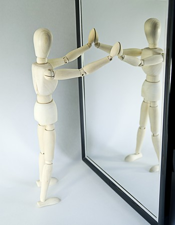 with reflection: Closeup of wooden mannequin looking in full length mirror, white studio background.