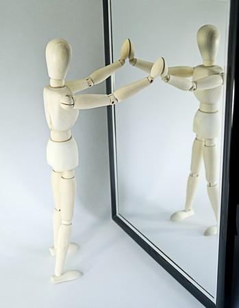 Detalle de madera maniquí mirando en espejo de longitud completa, fondo blanco de estudio.