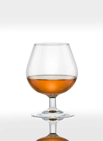 snifter: Cognac glass with brandy on a white background.