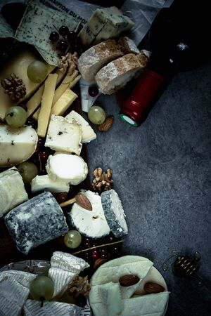 assorted cheeses, nuts and dried fruits on a black background. flat lay. copy space. 스톡 콘텐츠