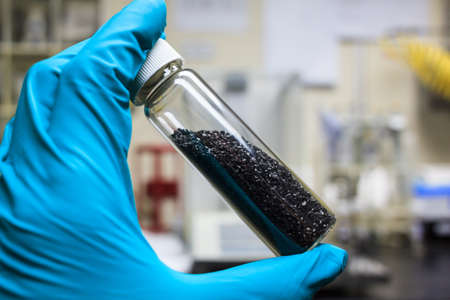 activated carbon charcoal coconut in clear bottom for use in laboratory, holding by green medical rubber hand glove. 스톡 콘텐츠