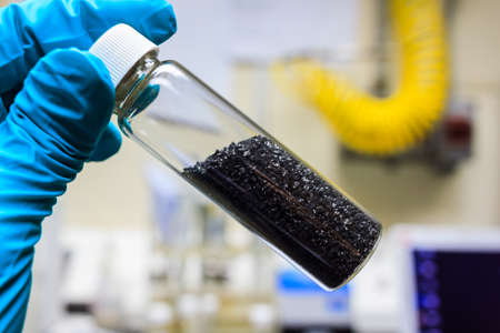 activated carbon charcoal coconut in clear bottom for use in laboratory, holding by green medical rubber hand glove. Archivio Fotografico