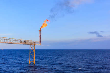 Offshore oil and gas flare blowout in the sea during day light background. Stock Photo