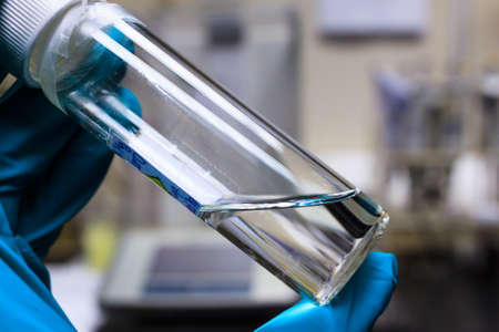 Chemical transparent liquid in clear bottle holding by chemistry hand in green chemical resistance glove. Foto de archivo