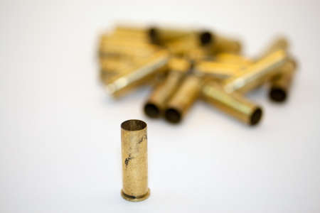 A collection of empty .38 caliber shell casings against a white background with the focus on the front one which is standing alone.