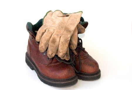 Werkschoenen en goed gedragen lederen werkhandschoenen op een witte achtergrond.