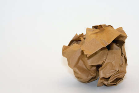 A crumpled piece of brown wrapping paper right of center on a white background with copyspace.