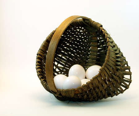 An egg basket, handwoven of white oak strips with white eggs inside. Stock Photo
