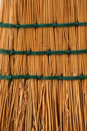 A closeup vertical image of tan boom straw with green stitching. Stock Photo