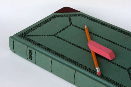 An old-fashioned green bookkeepers ledger book with pencil and eraser showing detail of the weave design of the cover.
