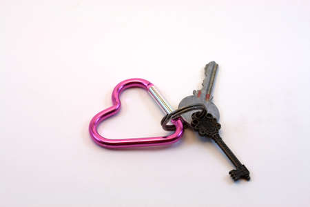 A pink heart shaped carabiner key ring with two keys on a white background.   Stock Photo