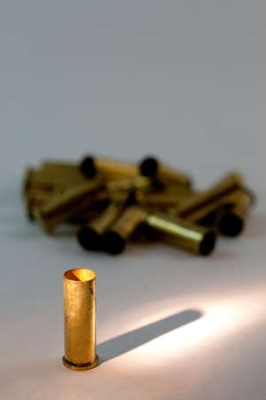 A group of emply .38 caliber brass shell casings with focus and spotlight on the front one.