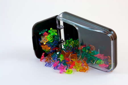 Brightly colored push pins in a variety of shapes spilling out of their overturned container. Stock Photo