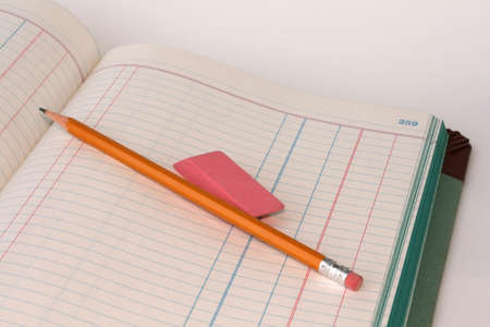 An old bookkeepers ledger book open to blank pages with a pencil and eraser. photo