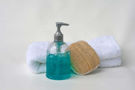 Aqua-blue gel in a pump dispenser in front of a folded white cotton towel and loofah sponge.