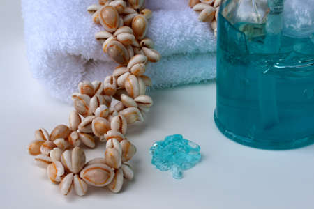 A dollop of blue-green foot massage gel dispensed next to a shell necklace, white cotton towel and pump bottle. Stock Photo