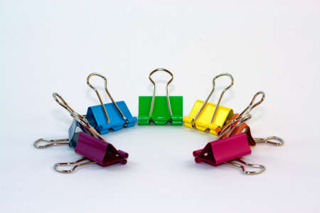 A group of colorful binder clips arranged in a semicircle on a white background.