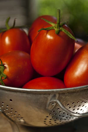 An old aluminum colander full of ripe Roma type tomatoes