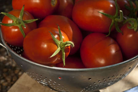 An old aluminum colander full of ripe red Roma type tomatoes