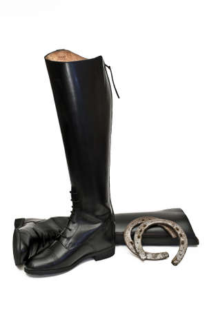 A pair of new black field boots used in equine competitions along with a pair of old custom made horse shoes
