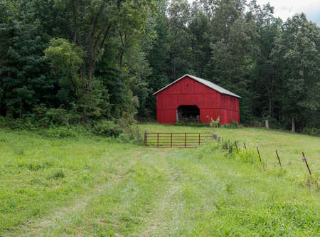 A typical sight in western Kentucky - red barn at woods edge with electric fence and tire tracks. Stock Photo