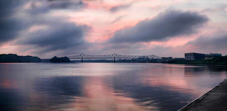 A purple and pink tinged sunrise over the Ohio river on a slightly foggy morning.