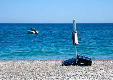 Stony beach with closed umbrella, closed chairs and a boat Stock fotó