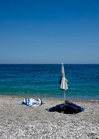 閉じた傘、椅子、タオルと石のビーチ 写真素材