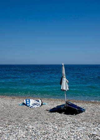 Stony beach with closed umbrella, chairs, and a towel