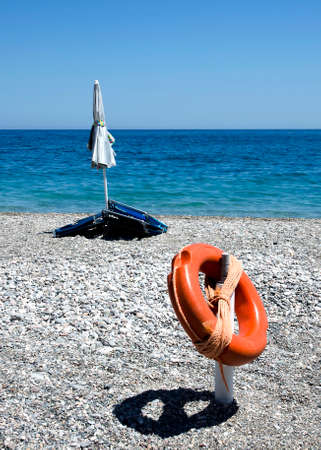 閉じた傘と救命浮環と石のビーチ