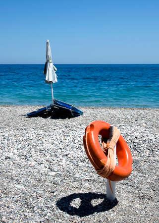 Stony beach with closed umbrella and a lifebuoy