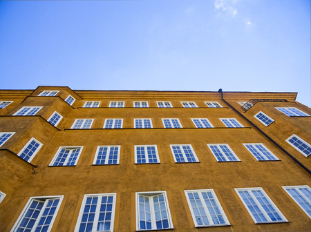 Looking Up at a Yellow-Orange Building with Blue Sky
