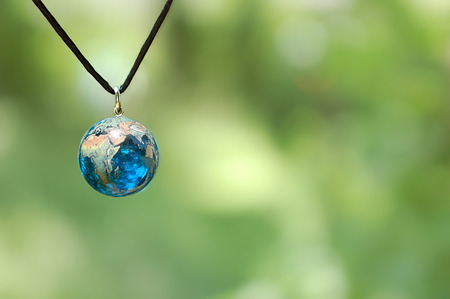 Blue Glass Earth Necklace on Green Background 版權商用圖片 - 118000707