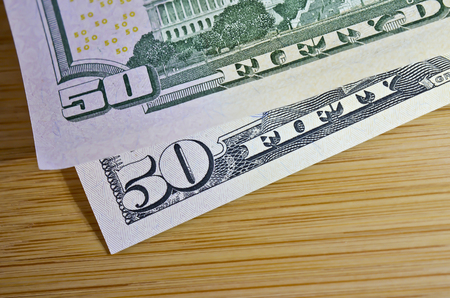 """Two Fifty Dollar Bills Reading """"Fifty-Fifty"""" on Wood Surface"""