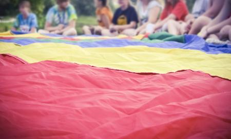 Colorido paracaídas con niños en segundo plano en clase de gimnasia Actividad al aire libre