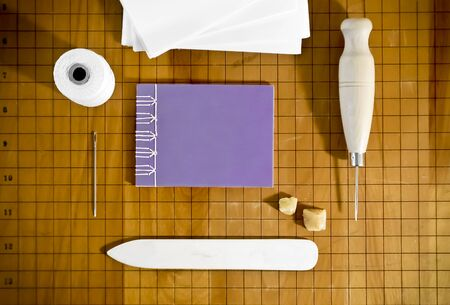 Bookbinding Materials with Small Purple Notebook on Wood Surface