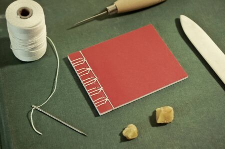 Small Red Stab Stitch Book Surrounded by Bookbinding Tools Banco de Imagens