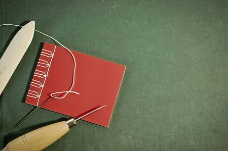 Hand Sewn Red Notebook with Bookbinding Tools on Green Background