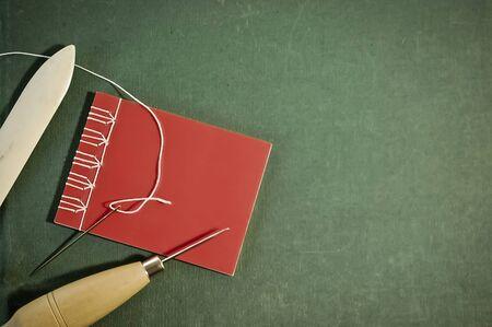 Taccuino rosso cucito a mano con strumenti di rilegatura su sfondo verde Archivio Fotografico