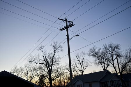 Dark Power Lines, Trees, and Houses with Evening Sky Banco de Imagens