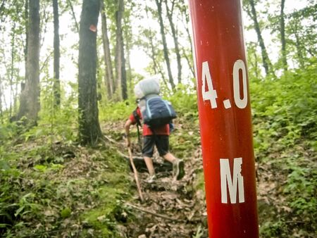 Young Hiker on the Trail with a 4 Mile Marker Foto de archivo