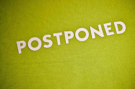"Word ""Postponed"" in White Paper Letters on Green Background Standard-Bild"